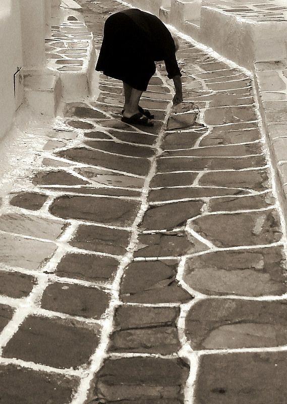 A Greek Yiayia is painting the alleyway, Chora, Mykonos Island, Greece * At work, focus, b/w