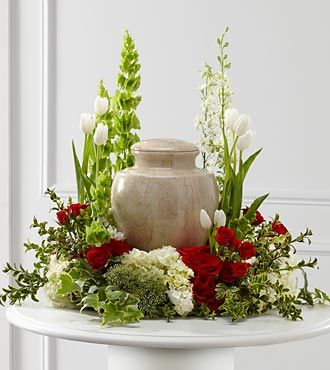 """The FTD® Tears of Comfort™ Arrangement is an elegant and sophisticated way to surround their urn with floral beauty at the final farewell service. Rich red roses and spray roses are vivid and bright amongst white tulips, larkspur, hydrangea and trachelium, accented with the bright greens of Bells of Ireland, hypericum berries, ivy and myrtle, creating a wonderful way to honor the life of the deceased.Approximately 21""""H x 24""""W.  Your purchase includes a complimentary personalized gift…"""