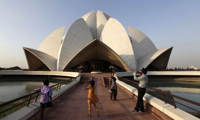 An Indian family takes photographs in front of the Lotus temple, Bahia faith, in New Delhi.  Despite regular maintenance, air pollution which may be the world's worst is damaging the building