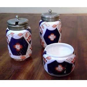 Victorian Gaudy Welsh (Imari) condiment set. Made in England circa 1880.  consists of an open salt, a peppershaker and a lidded mustard pot. The lids are marked EPNS but the silver plate   cobalt blue, coral and gilt patterns  The shaker and mustard pot are about 3 inches tall and 1¾ inches in diameter. The open salt is about 2 inches in diameter and 1¾ inches tall.