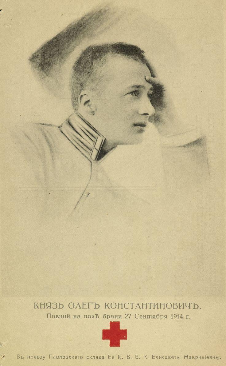 Postcard do Príncipe Oleg Constantinovich, em 1914. Ele está voltado para a direita com a mão esquerda levantada para a cabeça. Ele está vestindo uma jaqueta com gola alta. Há uma legenda em russo abaixo. Este cartão comemorativo foi produzido para arrecadar fundos para o trabalho de guerra de sua mãe, mas ele foi morto em ação antes de ter sido emitido.