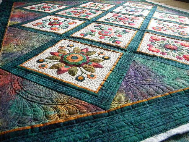 love the setting triangle quilting -love the paisley patterns & colors at the bottom of this one.