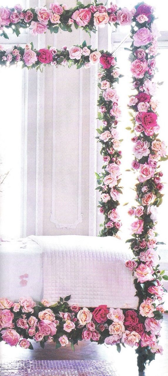 Four poster bed covered in flowers + light pink bedding