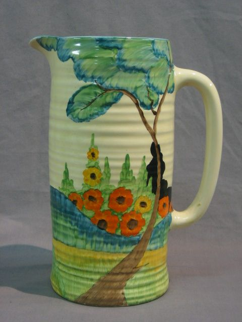 A large Clarice Cliff pottery jug decorated a garden scene with tree and flowers, the base marked Bizarre
