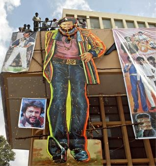 BACK WITH A BANG: Fans dodge the police to perform milk 'abhisheka' on Rajinikanth's cut-out at the Nataraj cinema in Bangalore on Friday.