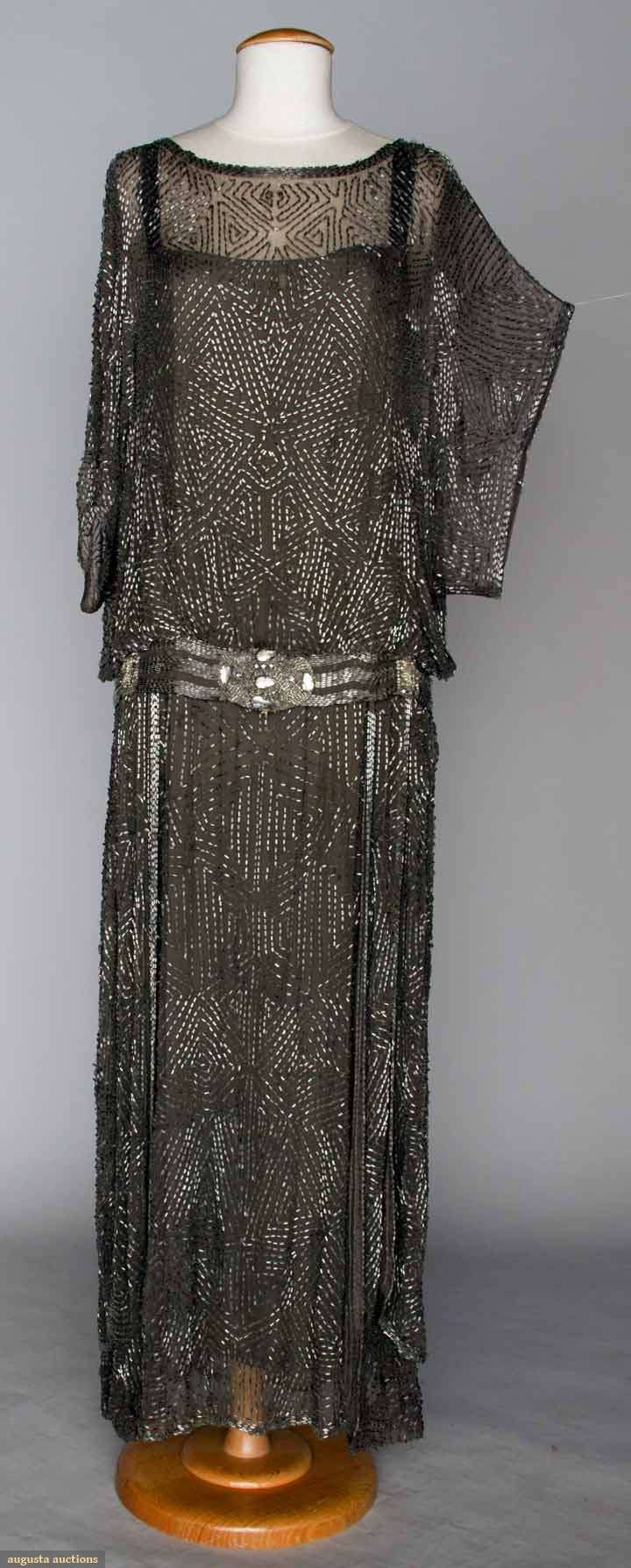 "SILVER BEADED DRESS, 1920s Dove gray silk chiffon, all-over beading in abstract geometric patterns, drop waist jeweled sash, B 34"", Drop W 36"", L 55"", (.5"" hole L shoulder & tiny tear on R, few loose beads) very good. MCNY via Augusta Auctions"
