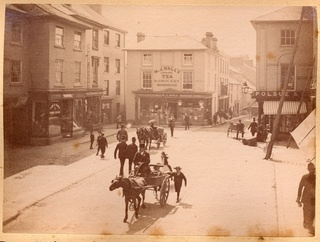 A photograph of Branwell's Corner in Penzance; the original Grocers shop here from 1829 was 'RM Branwell and Sons', belonging to JR Branwell's father, Robert Matthews Branwell. It is now known as Greenmarket, where Tregenza grocers is based. Others identifiable shops include 'Polsue &..' to the right, 'N.J Hall Genuine tea and grocery warehouse' in front, 'A.S ?? Maker' to the left and 'Fry & Sons Pure Cocoa' to the far left. Three horse and carriages are on the road, two of then in motion…