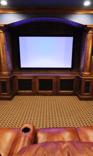 The large projector screen is tucked into a custom-built arched shelving unit with columns on either side. The dark wood and black wainscoting on the lower part of the walls is further dressed up by the patterned panels with nail-head trim.