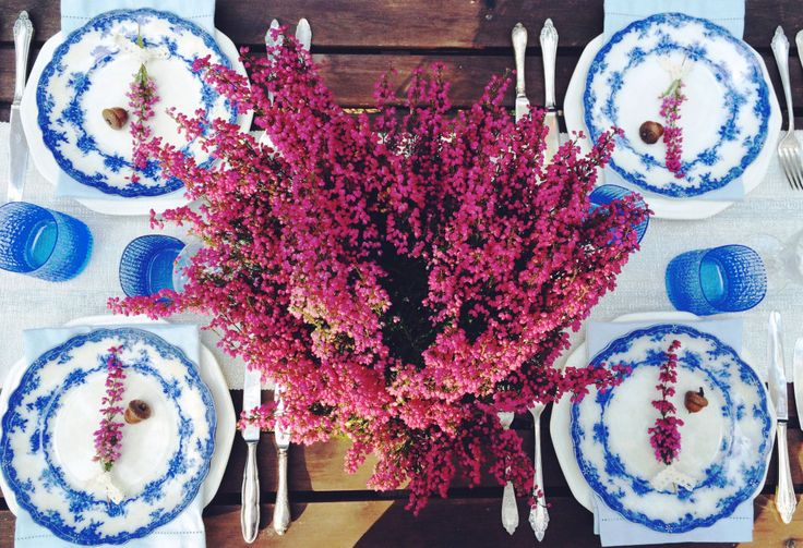 Outdoor, autumn dinner. Blue base tabletop. Heather on the table. Vintage cutlery. English porcelain.