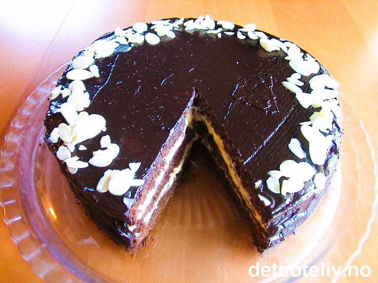 Her har du en av mine beste sjokoladekakeoppskrifter! Kakebunnen er utrolig saftig og myk og har veldig god smak av sjokolade. Kaken er fylt med ferdigkjøpt vaniljekrem og dekket med deilig sjokoladeglasur. Litt kaffelikør setter eksta piff på kaken, men kan sløyfes. Hvis du vil kan du pynte kaken med mandelflarn som på bildet, eller du kan velge helt annen pynt.
