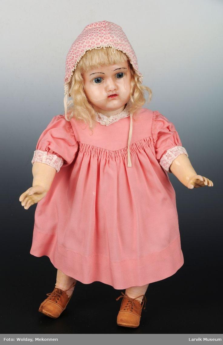 Funksjon/type: Dukke for lek. Voksdukke voks over composisjon. Hodet bygger på en grunnmodell av støpemasse. Over denne er det dyppet voks ofte i flere lag. Kroppen er tidlig type leddkropp med faste håndledd.  Form: Dukke med voks hode, har fullt undertøy på, små støvler. Har fått en liten kyse, noe den ikke hadde da museet fikk den. Men dukker hadde vanligvis noe på hodet.