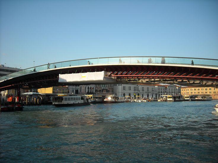 Vista laterale del ponte della Costituzione a Venezia con ponteggio in sospensione sul Canal Grande. Conosciuto anche come ponte di Calatrava, collega l'area della stazione degli autobus di Venezia (Piazzale Roma) con l'area ferroviaria (Stazione Santa Lucia).