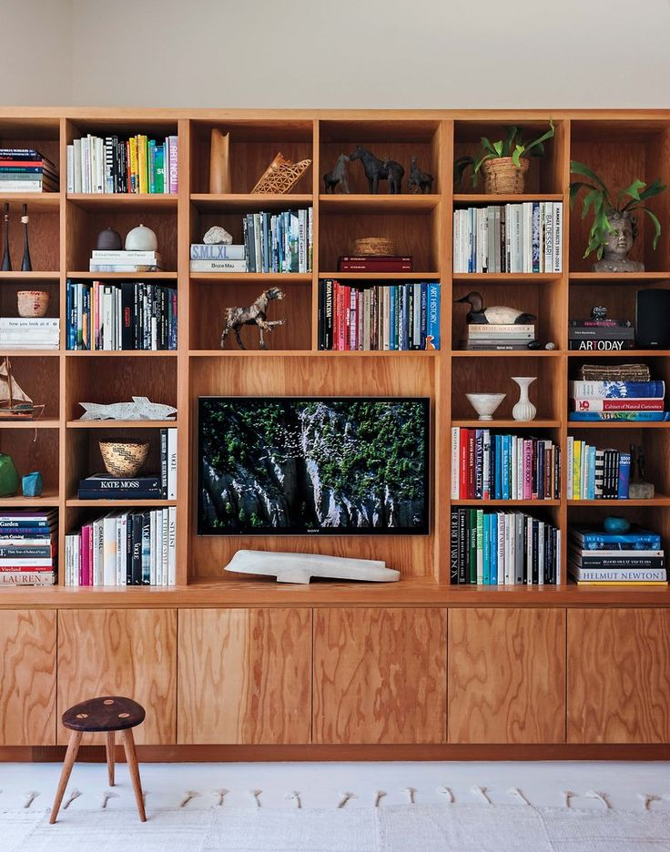 While the lower cabinets hide their son's toys and other unsightly clutter, the shelves artfully display the family's collection of books, trinkets, and of course, their television.