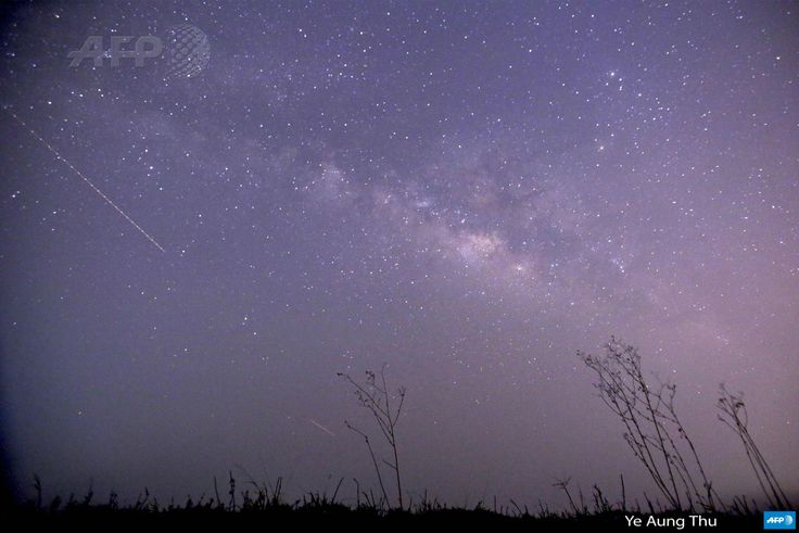 MYANMAR, Thanlyin : This long-exposure photograph taken on April 23,  2015 on Earth Day shows Lyrids meteors shower passing near the Milky Way  in the clear night sky of Thanlyin, nearly 14miles away from Yangon.  AFP PHOTO / Ye Aung Thu