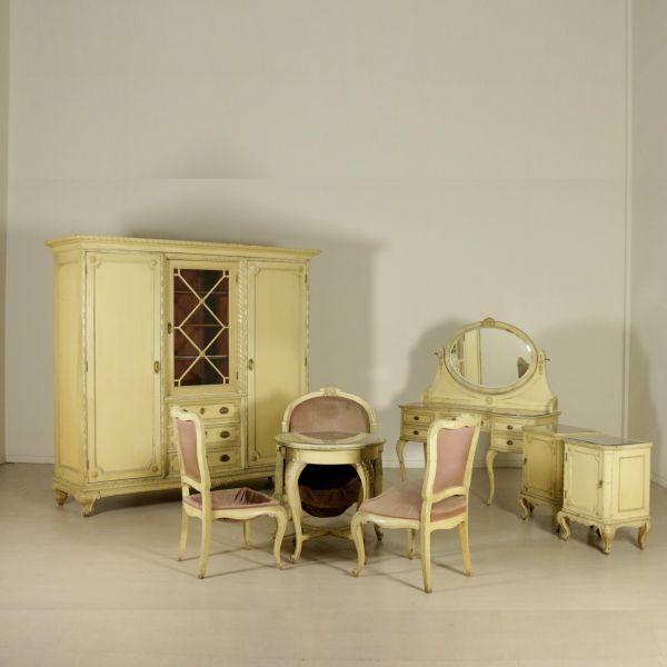 Riccamente intagliata presenta piani in cristallo. Composta da toilette (124x134x52), armadio (206x220x67.5), coppia comodini (70x52x37.5), tavolino (73.5x70), coppia sedie (97x55x60), poltrona (97x77x81.5).