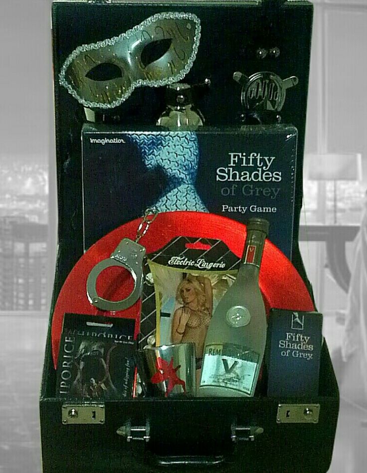 """Fifty Shades of Grey """"Shaken Not Stirred"""" Martini Kit Gift Basket made by Zotorius Creations Gift Baskets, LLC makes a nice Valentines Day Gift! Zotorius Creations Gift Baskets, LLC Like Us on Facebook! This basket consist of the Great British Cocktail Hamper (martini shaker, 2 martini glasses, strainer & spirit measure ); Silver and Grey Shades Mystery Bondage Kinky Kit (Handcuff/Satin Tie/Mask) with Steel Ben Wa Balls and Intimate Lubricant for Lovers; Official Fifty Shades of Grey…"""