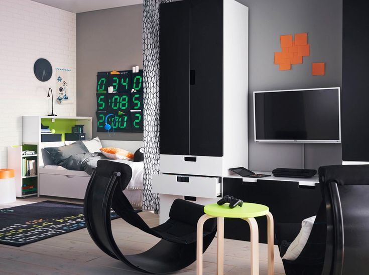 a teenage room with blackwhite bed and storage combined with two black balance chairs comfortable to sit in when playing video games