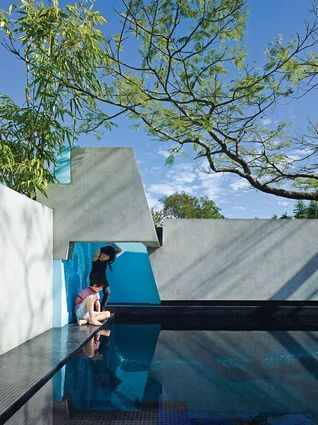 Sculptural elements tie the pool into the house's and garden's overall composition.