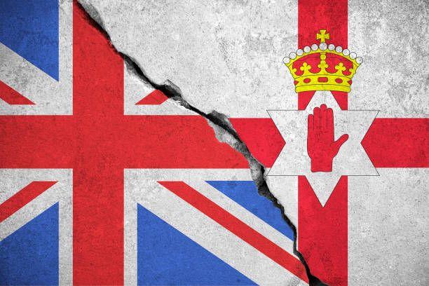north ireland flag on broken wall and half great britain flag north