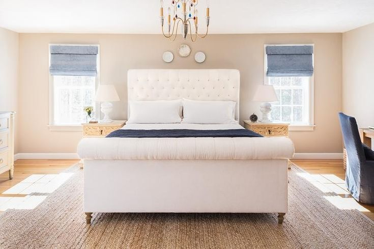 Cream and blue bedroom features a a trio of decorative plates over a cream tufted sleigh bed, ...