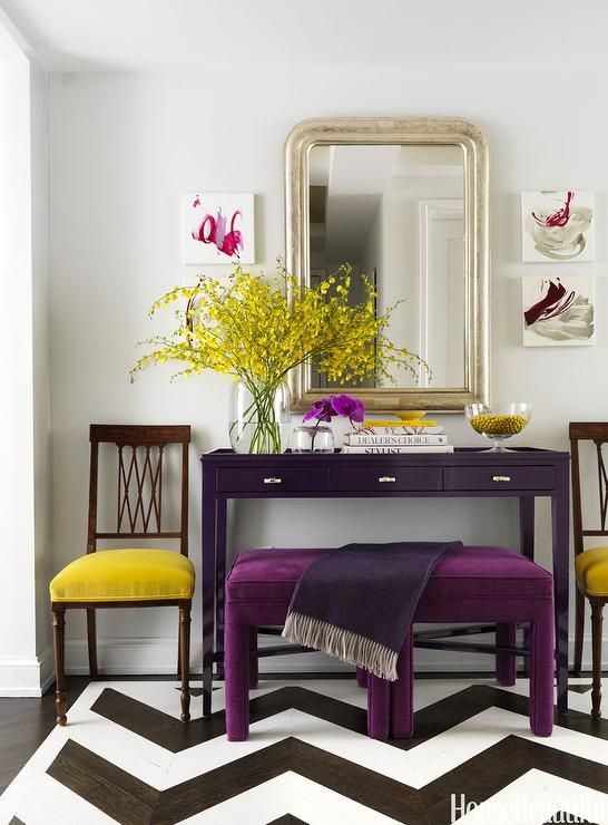 Christina Murphy - Contemporary yellow and purple foyer features a pair of purple velvets tools draped with a dark purple throw tucked under an aubergine console table topped with yellow and purple flowers placed under a silver leaf arched mirror.