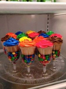 DIY cupcake stands - so colorful! Get plastic wine glasses from the dollar store, fill the bottom with M&M's (or color coordinating candies) and put the cupcakes on top. Great idea!