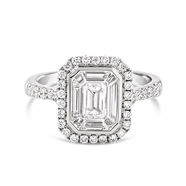 Ecali Presents: A magnificent central cluster of illusion set diamonds creates an emerald shape within a halo of round brilliant cut diamonds in this incredible engagement ring