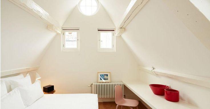 Boutique hotel a Bruxelles. Sembra una casa nella casa la stanza con la copertura a capanna. Si tratta di una camera sul tetto tutta bianca e con travi in legno antico dipinte di bianco anch'esse. Dove: 38 Rue des Bouchers, Brussels.