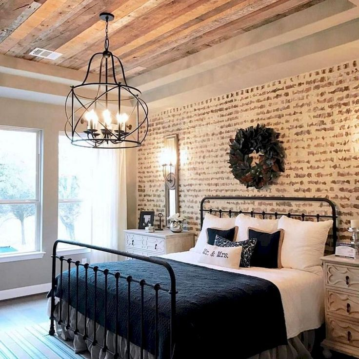 Beautiful bedroom! Exposed brick and a dark bed. It looks warm and cozy.