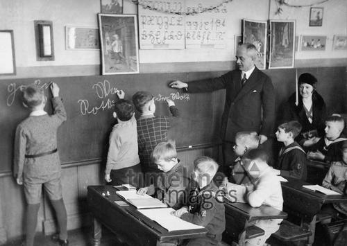 Schreibunterricht in der Schule, 1930 Timeline Classics/Timeline Images #30er #schwarzweiß #Fotografie #photography #historisch #historical #traditional #traditionell #retro #nostalgic #Nostalgie #Schule #School #Schüler #Lernen #Studieren #Bildungseinrichtung #Unterricht #Schulzeit #Ausbildung #Lehrer #Schulgebäude #Lehrerin #Hausaufgabe #Mitschüler #Schreiben #Klassenzimmer #Schulbank #Frontalunterricht #Schreibunterricht #Tafel