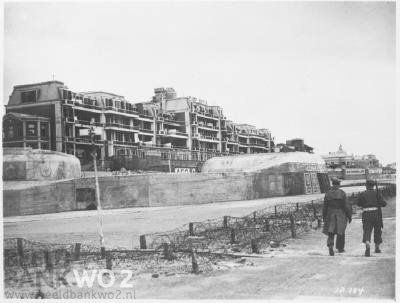 """Duitse vernielingen, afbraak, versterkingen in Den Haag. Betonnen muur op de Boulevard van Scheveningen. Het strand is geheel bezet met """"asperges"""".  Beeld Datum Periode: januari 1945"""