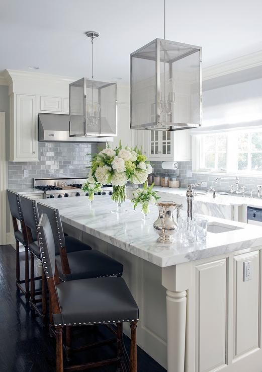Ivory and gray kitchen features ivory cabinets paired with white marble countertops and a gray subway backsplash tiles.