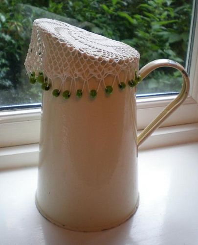 P6210398 by Pea Knits..., via Flickr. Although this is crocheted (which I don't know how to do), need to find a knitted doily/jug cover and put beads around the edge so it stays in place. Love the look, and it's so practical.
