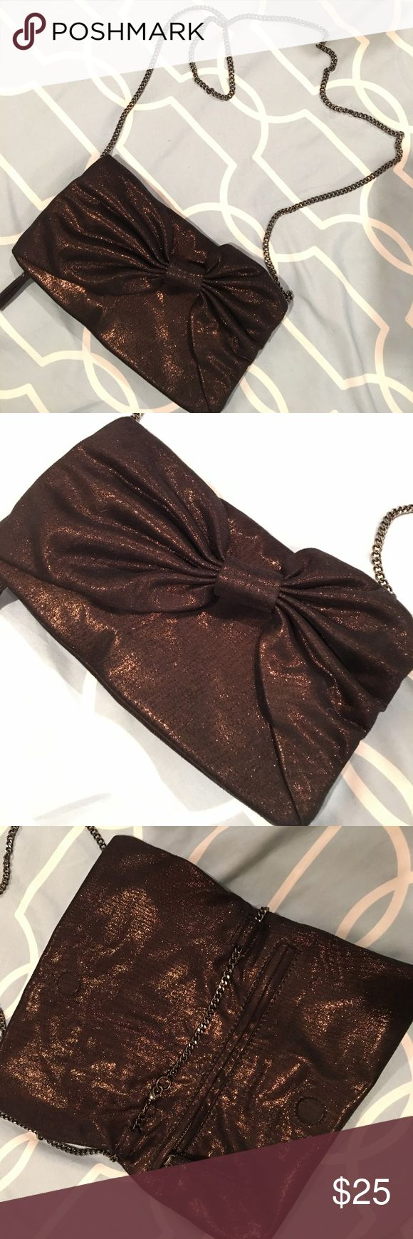 Gap Brown Shiny Bow Purse Soft, relaxed material, with a chain that can be worn lengthwise or cross body. It's a fold over design with a magnetic closure. Once unzipped, opens into a main compartment. Strap can also be detached and this can be worn as a clutch. GAP Bags
