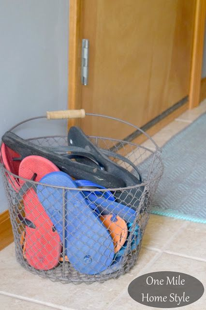 No more tripping over all those flip flops at the front door! Keep your summer organizing easy by tossing sandals in a simple wire basket. - Summer Home Tour   One Mile Home Style