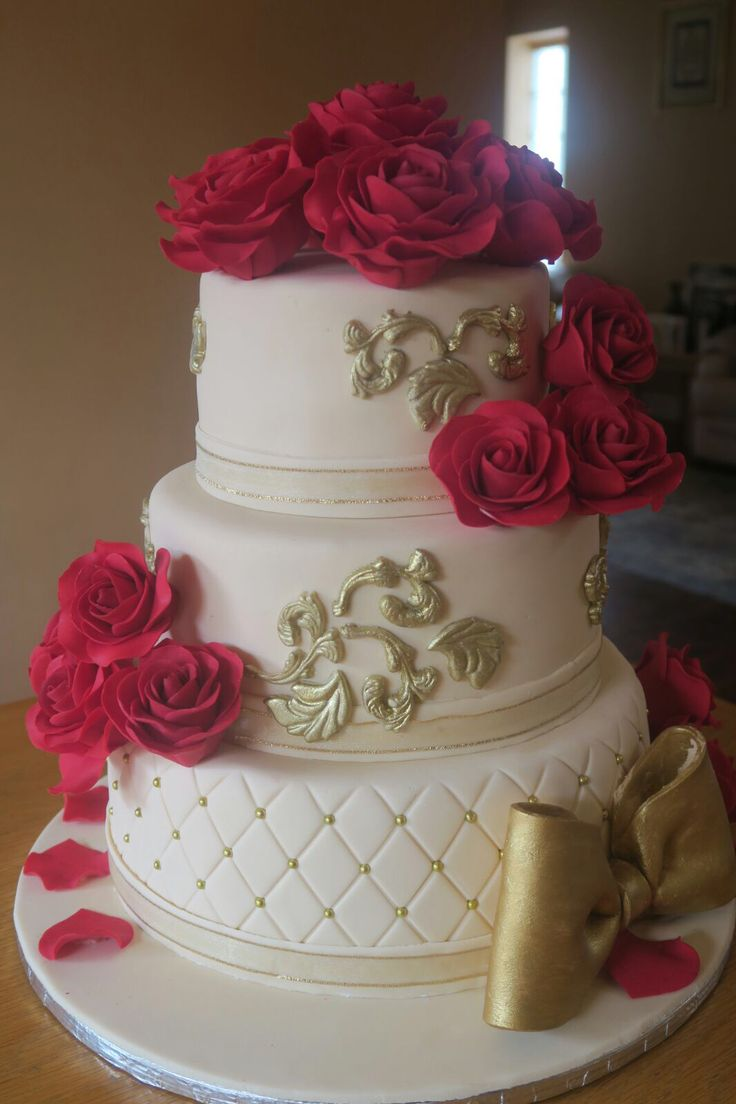 Beautiful ivory and gold cake with red sugar roses.