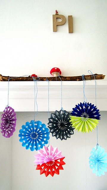 Such a cute display idea: a branch over the doorway.  I would paint the branch white, or maybe a bright color like pink or blue.  My dangly things would be orbs on mine.  The little mushrooms in this display are cute!  (Click for directions for making dramatic cutout paper circles.)