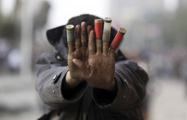 A protester against President Mohamed Mursi shows expended shotgun cartridges that he said were fired by riot police during clashes along Qasr Al Nil bridge, which leads to Tahrir Square in Cairo, on January 27, 2013. (Photo by Amr Abdallah Dalsh/Reuters/The Atlantic)