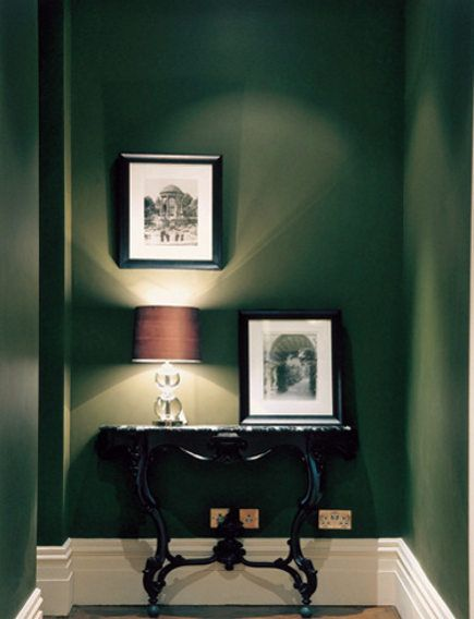 dark green painted walls. perfect for a hallway or anywhere with a yellow, tufted sofa.