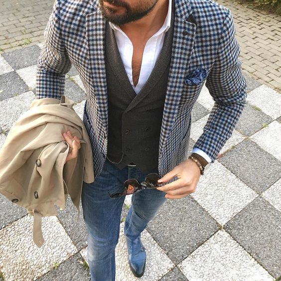 Consider teaming a nude trenchcoat with blue slim jeans to look classy but not particularly formal. Channel your inner Ryan Gosling and throw in a pair of blue leather double monks to class up your look.   Shop this look on Lookastic: https://lookastic.com/men/looks/trenchcoat-blazer-waistcoat/18986   — White Dress Shirt  — Blue Paisley Pocket Square  — Olive Wool Waistcoat  — Blue Gingham Blazer  — Beige Trenchcoat  — Olive Watch  — Blue Skinny Jeans  — Blue Leather Double Monks
