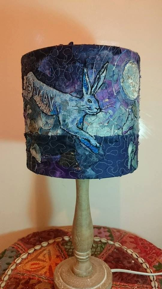 Hare lampshade,20 cm drum, embroidered lampshade, statement lampshade, contemporary lampshade, moon gazing hare, hare table lamp, blue This exquisitely stitched leaping hare lampshade has been created using teenie tiny scraps of fabric that have been free motion machine embroidered with emphasis on the finer details and the passion and love with which is was made really shines through. It is a 20 cm table lamp drum shade and does not include the stand. When lit the light shines through the…