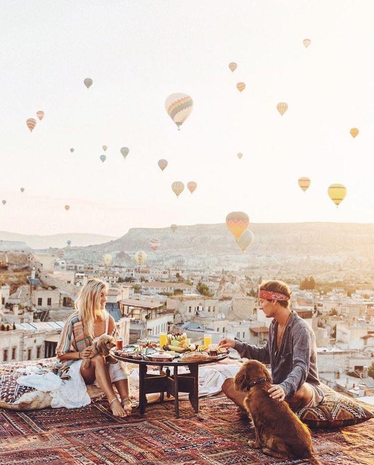 Ein Frühstück auf der Terrasse und im Horizont ist der ganze Himmel voller Heißluftballons. Kapadokien, Türkei