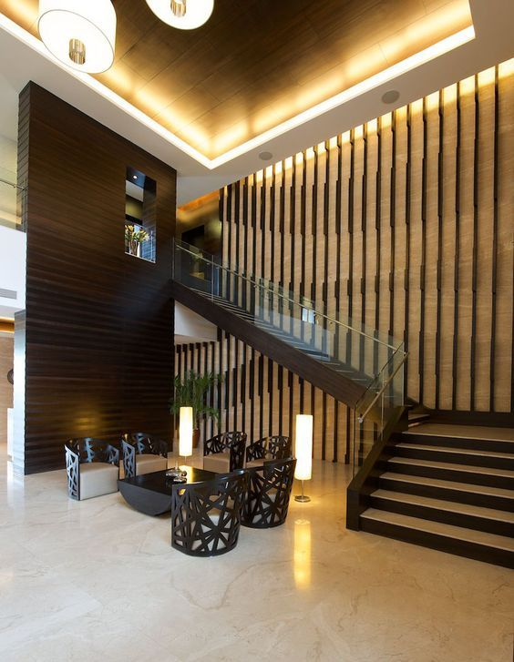 The entrance lobby to the clubhouse is the key space at Luxuria, designed by Kapadia Associates. The lobby is double height, with traventino marble clad walls. The staircase that leads above from the lobby, is flanked by a feature wall. This wall is a series of curves created by playing with wooden fins. The staircase leads to a spacious gymnasium, indoor games room, a health centre and business centre.  #elegance #interiordesign: