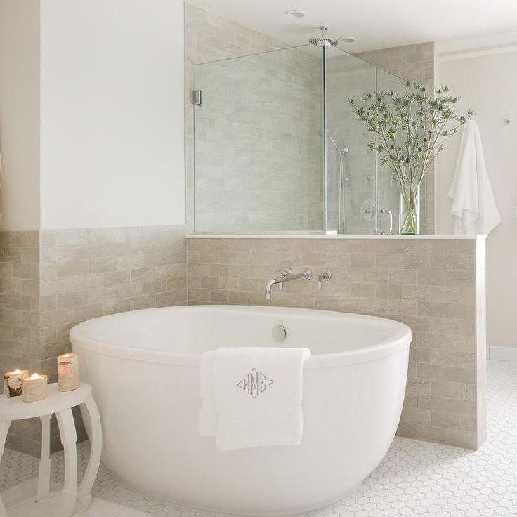 Restful bathroom is equipped with a white oval tub placed on white hex floor tiles beside a white side table and against light taupe wall tiles.