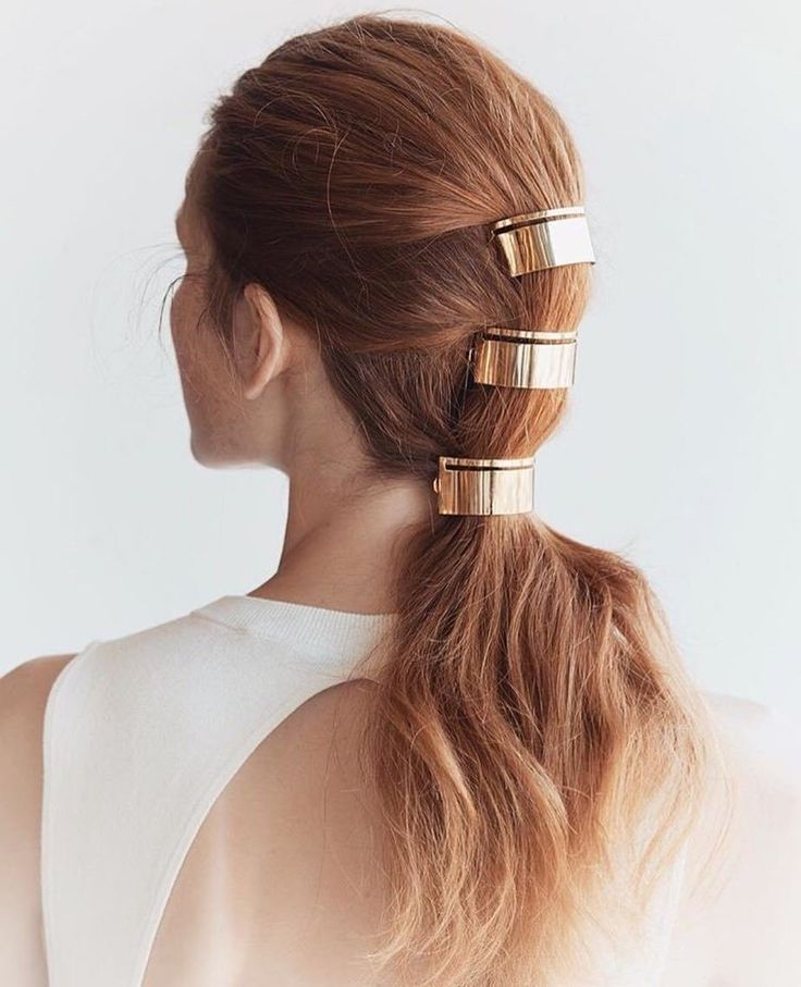 pull your hair back into a half-up style, and secure with an elastic. Halve the remaining hair underneath and fasten into ANOTHER ponytail. The final pony should be the loosest of all — and while you don't HAVE to add sleek metal clips, you definitely can.