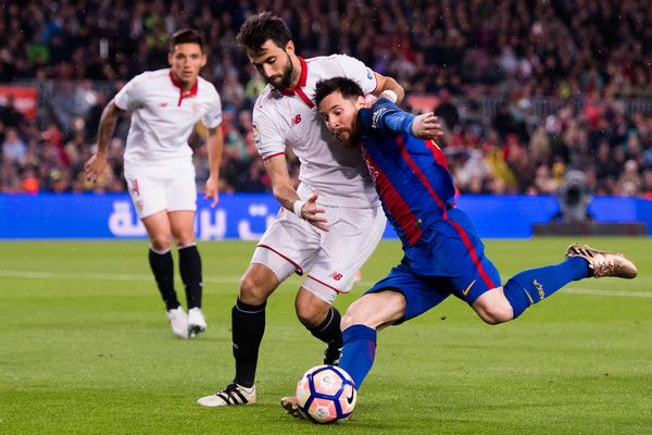Lionel Messi of FC Barcelona shoots on goal under pressure of Nico Pareja of Sevilla FC during the La Liga match between FC Barcelona and Sevilla FC at Camp Nou stadium on April 5, 2017 in Barcelona, Catalonia.