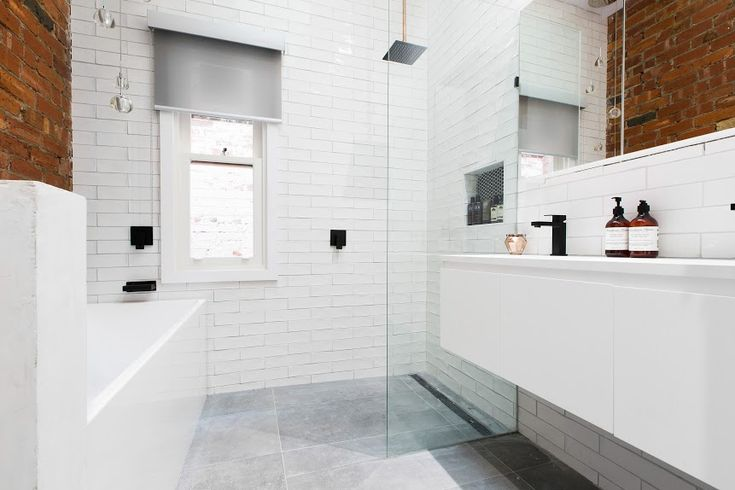 Coolest industrial bathroom with exposed red brick and white handmade subway tiles and black tapware. The concrete look grey tiles are also perfect in this space!