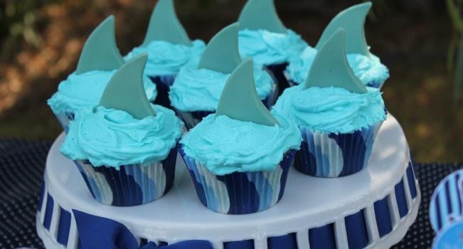 Para una fiesta marina, cupcakes decorados con una aleta de tiburón hecha de chocolate.