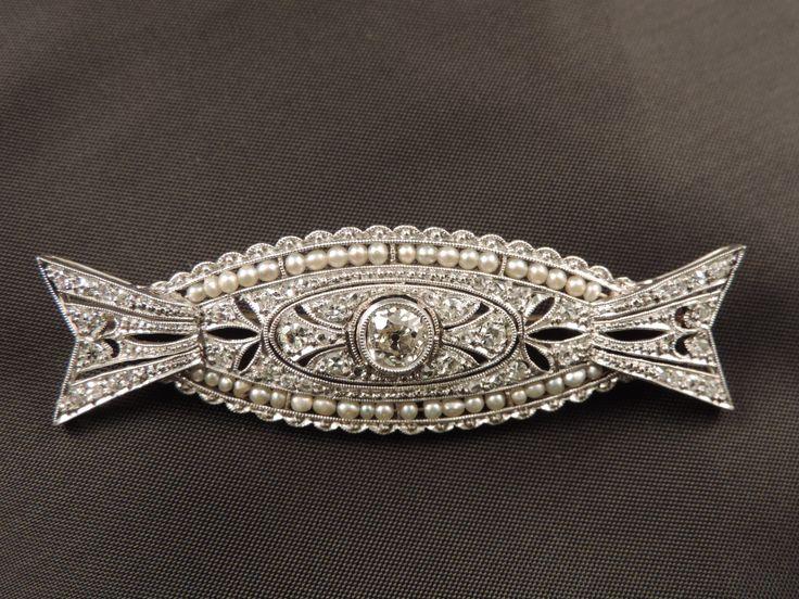 Spilla in platino francese di epoca Art Déco (1925-40) caratterizzata da una lavorazione ad intaglio, imitante il pizzo. Tempestata di diamanti per un totale di 0,40 punti di carato circa, è impreziosita, al centro, da un diamante, taglio cuscino, di mezzo carato circa e, sui lati, da due file di piccole perle naturali. In vendita su www.mirabilia.gallery per 3.090,00 € (Iva inclusa).