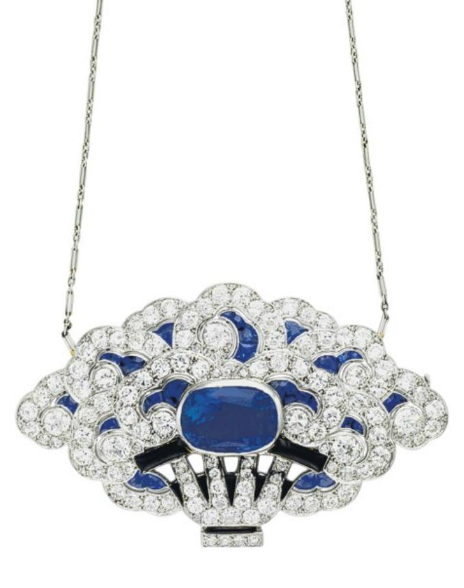 AN ART DECO SAPPHIRE AND DIAMOND PENDANT NECKLACE, CIRCA 1925. Suspending a pendant brooch, designed as a blooming potted plant, the billowing old-cut diamond and calibré-cut sapphire blossoms centring upon a cushion-cut sapphire, to the old-cut diamond stems and pot with black enamel and onyx detail, to the fine link platinum neckchain, 2 3/4 ins., with French assay mark for platinum. #ArtDeco #pendant #brooch